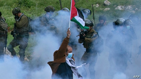 A Palestinian protester raises a national flag as a member of the Israeli  forces points his gun, amid smoke from tear gas…