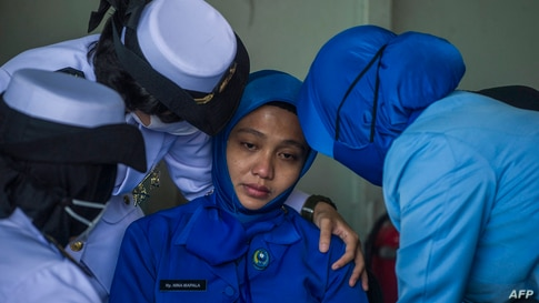 Military personnel console a sailor's wife during a remembrance ceremony for the crew of the Indonesian navy submarine KRI…