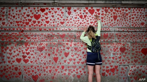 A woman draws on the National Covid Memorial Wall on the embankment on the south side of the River Thames in London on April 30…