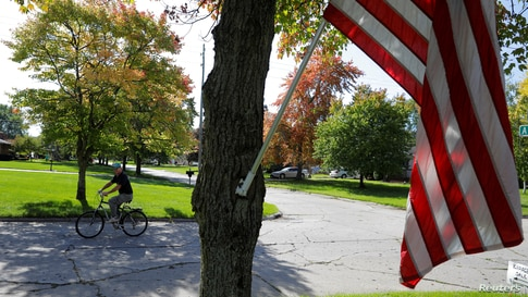 A bicyclist rides through a neighborhood in Saginaw Township, Michigan, October 10, 2019.