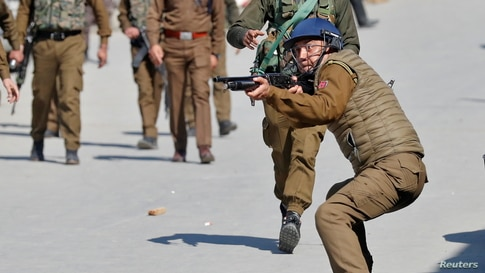 An Indian police officer aims his pellet gun towards demonstrators during a protest after Friday prayers in Srinagar March 5,…