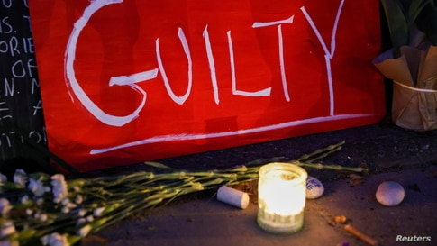 """A sign reading """"GUILTY"""" rests next to a candle at Carl Schurz Park after the verdict in the trial of former police officer…"""