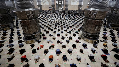 Muslim men maintain social distancing as they attend Friday prayers during the holy fasting month of Ramadan at the Great…