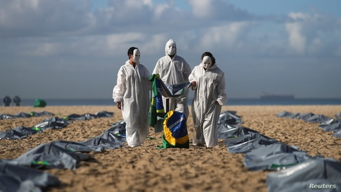 Activists from NGO Rio de Paz carry a Brazilian flag as they display hundreds of plastic bags, representing dead bodies, during…