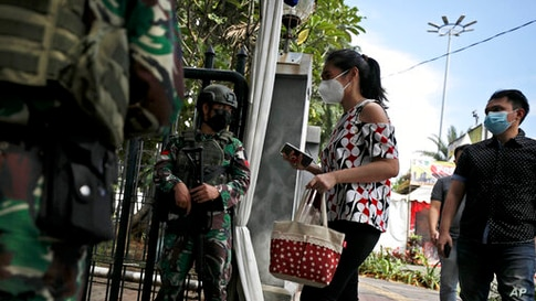 In the wake of a church attack in South Sulawesi on March 28, soldiers check worshippers at the entrance of the St. Mary of the…