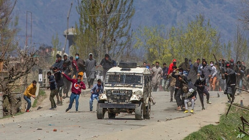 Kashmiri villagers throw stones and bricks at a police vehicle during a protest near the site of a gunbattle in Pulwama, south…