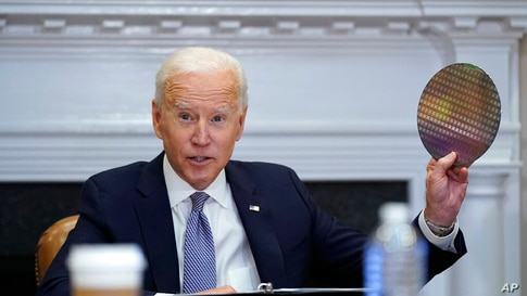 President Joe Biden holds up a silicon wafer as he participates virtually in the CEO Summit on Semiconductor and Supply Chain…