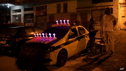 Illuminated crosses are displayed on top of a salesman's car outside Saint George Church, closed to help contain the spread of…
