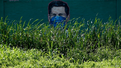 A mural by artist Gabo Luna features a health worker with a mask to protect him from COVID-19 in a street in Almirante Brown,…