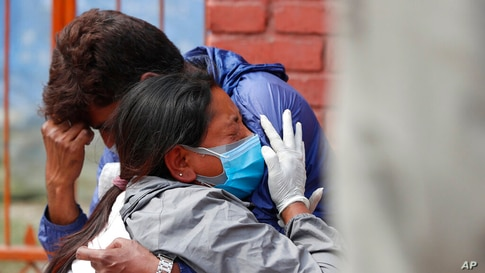 Relatives of a person who died of COVID-19 mourn at a crematorium in Kathmandu, Nepal, Friday, April 30, 2021. An infection…