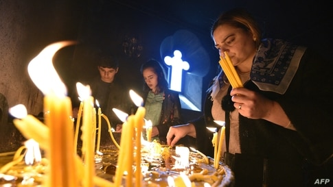 Armenian Christian worshippers light candles during an Easter religious service in Yerevan.