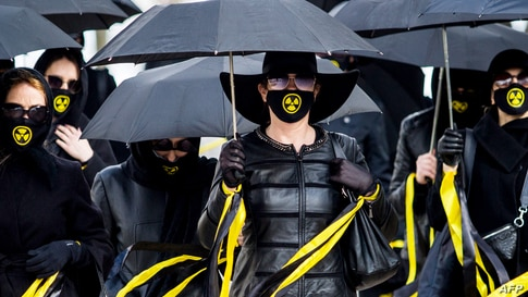 Women wearing black clothing and face masks with radioactivity sign march under umbrellas in Minsk, Belarus, to commemorate the victims of the Chernobyl nuclear disaster on the 35th anniversary of the tragedy.