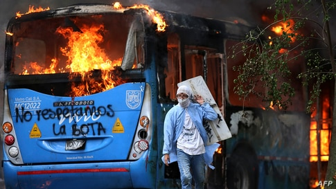 A man walks in front of a public transportation bus in flames during a protest against a tax reform bill launched by Colombian President Ivan Duque, in Cali, April 28, 2021.