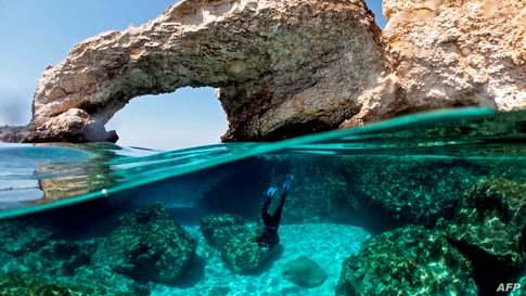 Cypriot marine ecologist Louis Hadjioannou dives to photograph the coral as he monitors the impact of climate change in the crystal clear waters of Glyko Nero in Ayia Napa, off the island's southeastern shore, Cyprus.