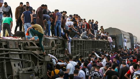 People climb an overturned train carriage as they gather at the scene of a railway accident in the city of Toukh in Egypt's central Nile Delta province of Qalyubiya, April 18, 2021.