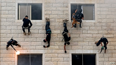 Palestinian members of Hamas' security forces rappel along the wall of a building as they show off their skills during a police graduation ceremony in Gaza City.