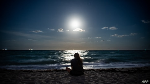 A Super Pink Full Moon lights up the sky as a person relaxes on the beach in Miami Beach, Florida, April 26, 2021.