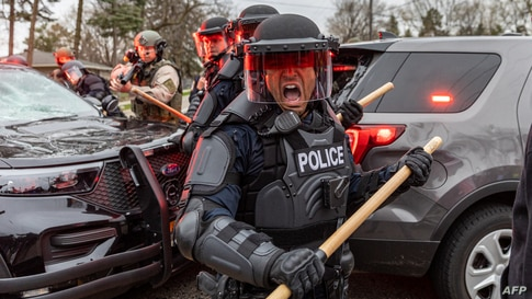 Police officers take cover as they clash with protesters after an officer shot and killed a black man in Brooklyn Center, Minneapolis, Minnesota, April 11,2021.