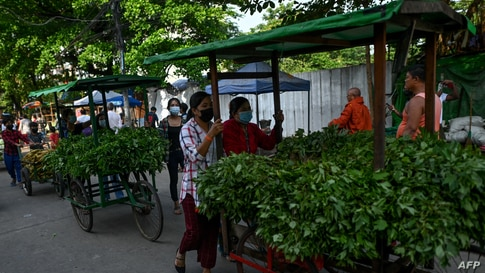 "People push carts with vegetables for distribution during a ""Donate your extras, take what you need"" - a donation drive aimed at helping low income households - in Thaketa township in Yangon as communities cope with an economic downturn in Myanmar."