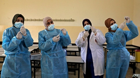 Palestinian health ministry workers prepare doses of the Sinopharm COVID-19 coronavirus vaccine, donated by the Chinese government, at a school in Halhoul, north of Hebron in the occupied West Bank.