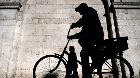 A man rides a bicycle during a sunny morning in central Moscow, Russia.