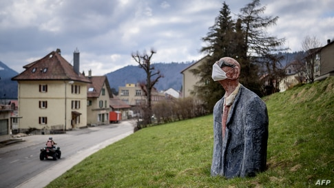 A sculpture representing a man wearing a facemask is seen as a preventive measure against the Covid-19 coronavirus in a field in Saint-Croix, Switzerland.