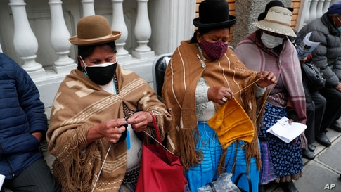 Women knit while waiting for the AstraZeneca vaccine for COVID-19 at a government-run social security clinic during vaccinations for people over age 80 in La Paz, Bolivia.