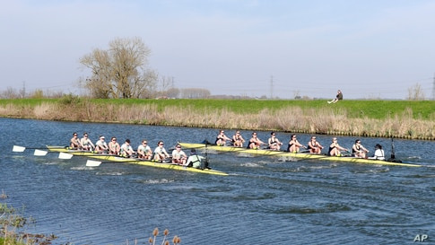 The Oxford, right, and Cambridge boats compete during the Varsity Women's Boat Race on the Great Ouse river at Ely in Cambridgeshire, England.