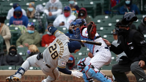Milwaukee Brewers' Daniel Robertson (28) is hit on the head by a pitch as Chicago Cubs catcher Willson Contreras reaches for the ball during the ninth inning of a baseball game in Chicago, Illinois, April 25, 2021.