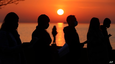 Parishioners are silhouetted against the rising sun as they pray during an Easter sunrise service held by Park Community Church at North Avenue Beach in Chicago, Illinois.