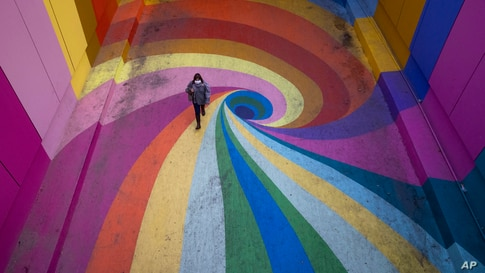 A woman walks through the rainbow-colored Paseo Bandera in Santiago, Chile, April 27, 2021, which is empty due to the coronavirus pandemic.