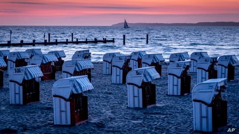 Beach chairs are lined up at the Baltic Sea before sunrise in Travemuende, northern Germany.
