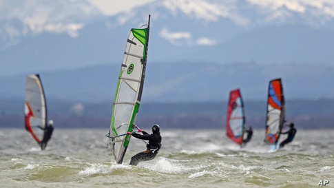 Surfers brave high winds to speed on the waves at lake Ammersee in front of the Alps near Herrsching, Germany.