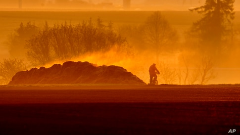 A man rides his bike past a steaming dunghill as the sun rises in Frankfurt, Germany.