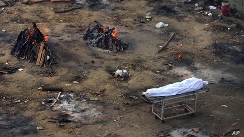 Multiple funeral pyres of people who died of COVID-19 are seen burning at a ground that has been converted into a crematorium for mass cremation of coronavirus victims, in New Delhi, India, April 21, 2021.