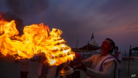 """A Hindu priests perform an evening ritual """"Aarati"""" at Sangam, the confluence of the rivers Ganges and Yamuna on Ramnavami in Prayagraj, India."""