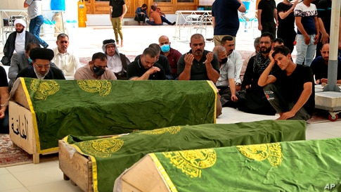 Mourners pray for coronavirus patients who were killed in a hospital fire, during their funeral at the Imam Ali shrine in Najaf, Iraq.