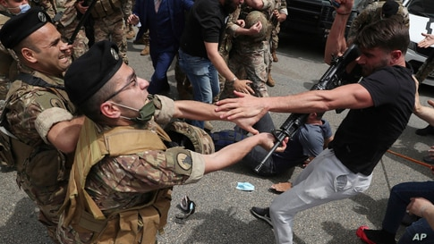 An opponent of Judge Ghada Aoun grabs the weapon of a soldier, after he was hit, during a sit-in outside the Justice Palace in Beirut, Lebanon.