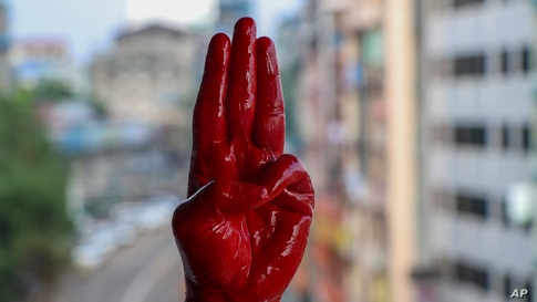 An anti-coup protester shows the three-fingered salute of resistance on his red painted hand in memory of protesters who lost their lives, in Yangon, Myanmar.