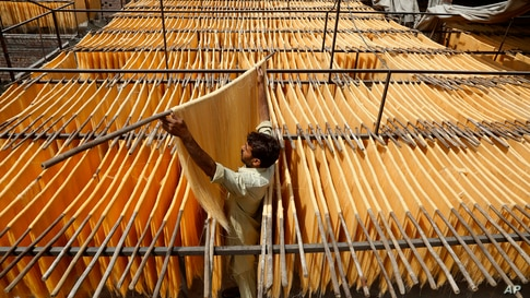 A vendor arranges traditional vermicelli noodles, a favorite during the Muslim's holy fasting month of Ramadan, at a factory, in Lahore, Pakistan, Tuesday, April 27, 2021. (AP Photo/K.M. Chaudary)