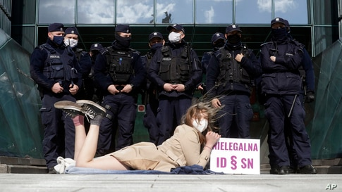 Policemen guard Poland's Supreme Court as a protester lies on the pavement in Warsaw.