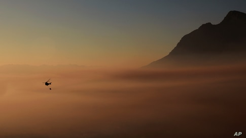 A helicopter hovers above the smoke which engulfs the city of Cape Town, South Africa.