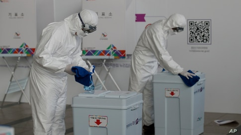 Workers wearing protective gears disinfect ballot boxes ahead of the early voting for the upcoming Seoul mayoral by-election at a local polling station in Seoul, South Korea.
