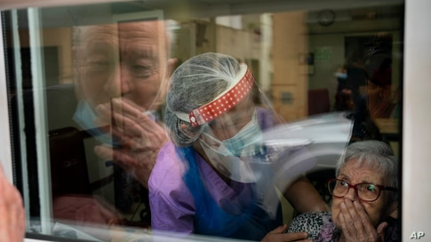 Javier Anto, 90, and his wife Carmen Panzano, 92, blow kisses to one another through the window at a nursing home in Barcelona, Spain.