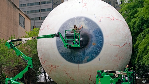 Workers restore the fiberglass sculpture called the Eyecreated by artist Tony Tasset in downtown Dallas, Texas.