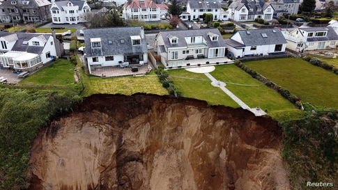 Houses are seen on the edge of a cliff after it collapsed in the village of Nefyn, Wales, Britain.