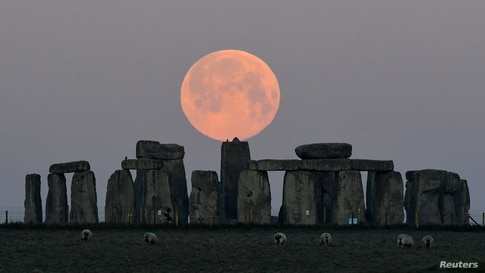 """Sheep graze as the full moon, known as the """"Super Pink Moon"""", sets behind Stonehenge stone circle near Amesbury, Britain."""