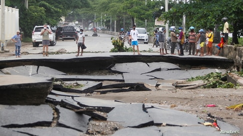 People stand near roads damaged by floods after heavy rainfall in Dili, East Timor.