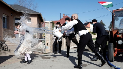 Members of the Hungarian dance and folk art ensemble Marcal throw water at a woman as part of traditional Easter celebrations in Gyor-Menfocsanak, Hungary.