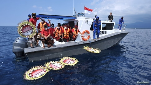 People throw flowers and petals with names of the sunken KRI Nanggala-402 submarine crew members from the boat during a prayer at the sea near Labuhan Lalang, Bali, Indonesia.